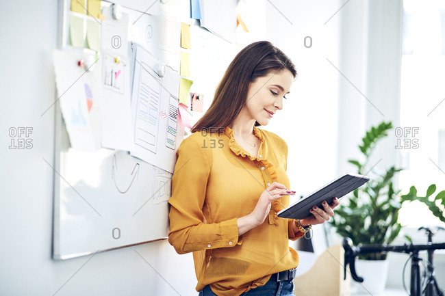 Smiling businesswoman using tablet at whiteboard in office