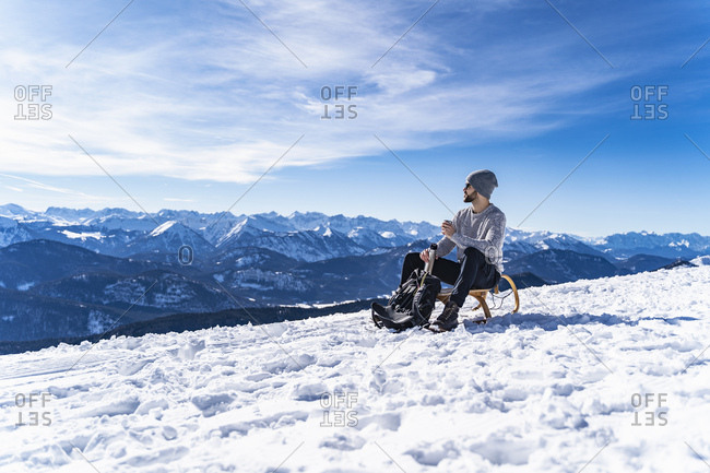 Germany- Bavaria- Brauneck- man in winter in the mountains having a break