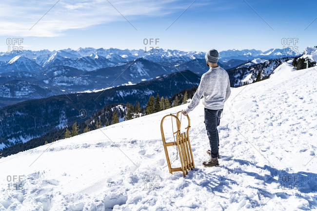 Germany- Bavaria- Brauneck- man with sledge in winter in the mountains looking at view