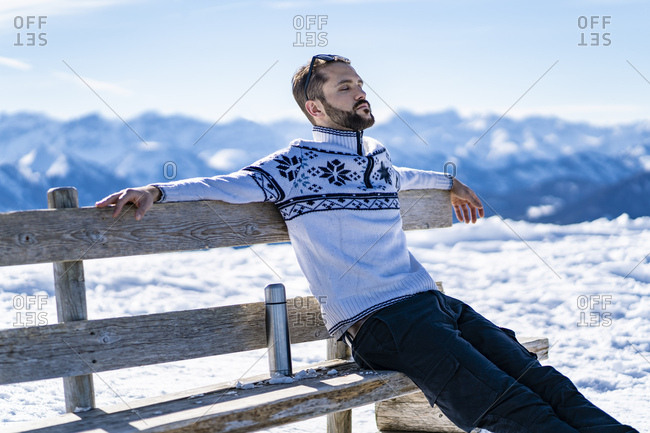 Germany- Bavaria- Brauneck- man sitting on bench in winter in the mountains having a break