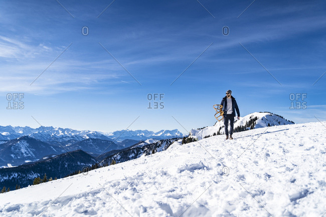 Germany- Bavaria- Brauneck- man carrying sledge in winter in the mountains