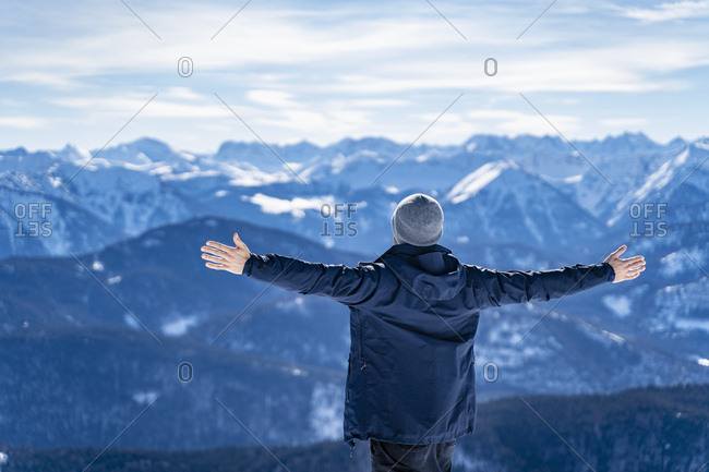 Germany- Bavaria- Brauneck- man in winter enjoying the view in the mountains