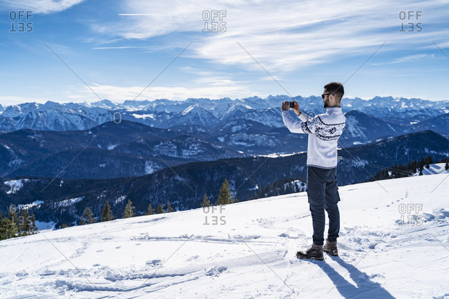 Germany- Bavaria- Brauneck- man in winter in the mountains taking a picture