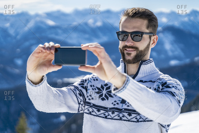 Germany- Bavaria- Brauneck- man in winter in the mountains taking a selfie