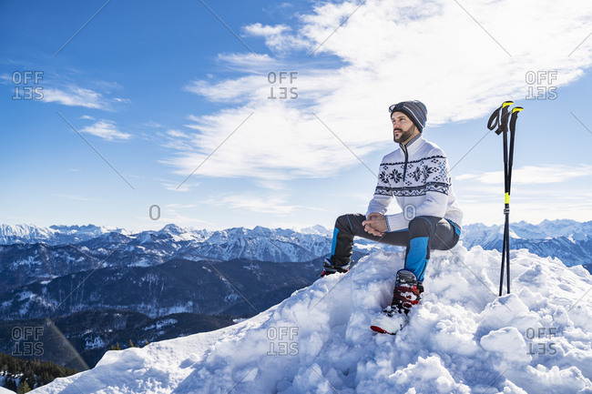 Germany- Bavaria- Brauneck- man in winter sitting on mountaintop