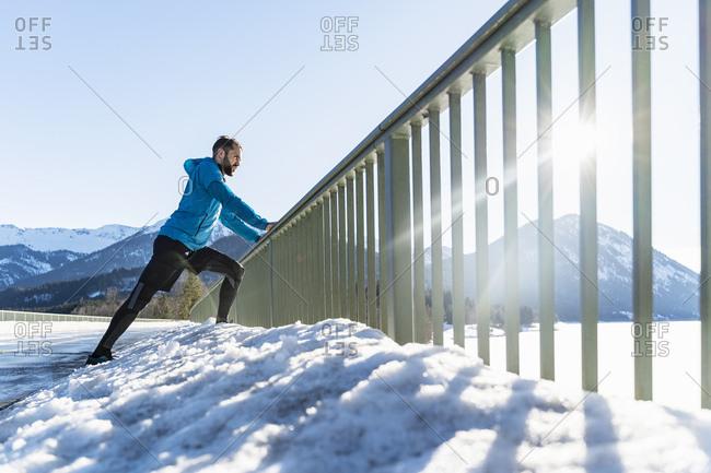 Germany- Bavaria- sportive man stretching in winter on bridge railing