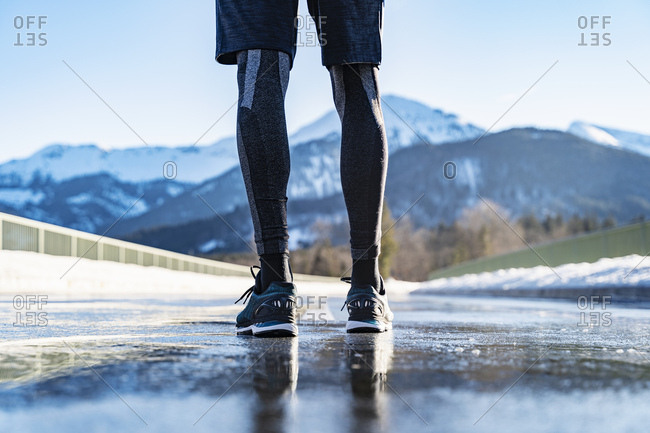 Germany- Bavaria- legs of sportive man standing on a road in winter
