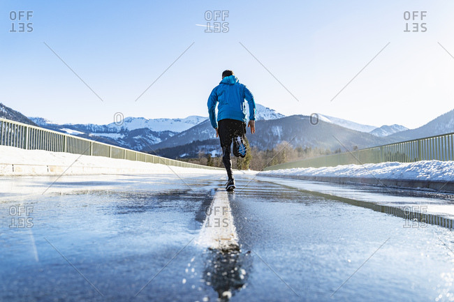 Germany- Bavaria- sportive man running on a road in winter