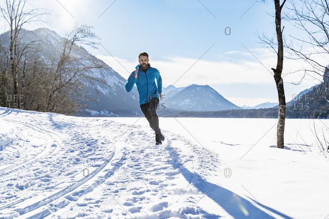 Germany- Bavaria- sportive man running through snow in winter