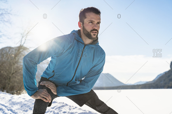 Germany- Bavaria- sportive man stretching in winter