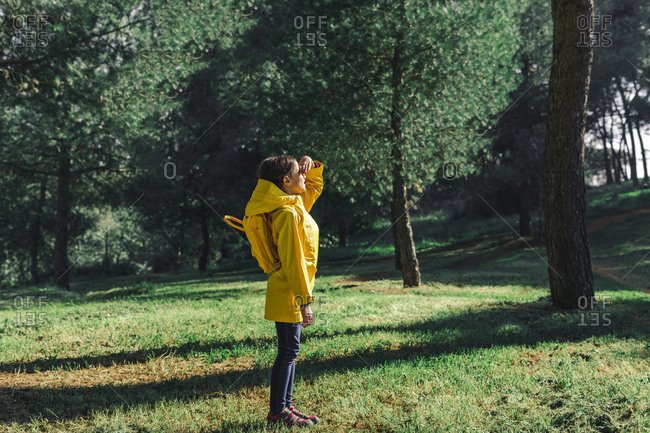 Girl wearing yellow raincoat and yellow backpack standing on a meadow at sunlight