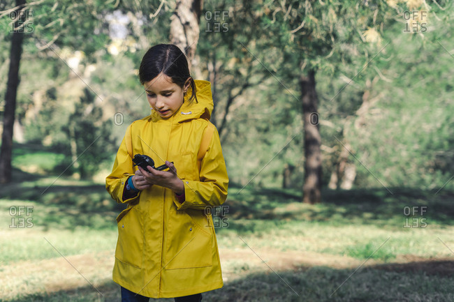 Girl wearing yellow raincoat in nature looking at compass