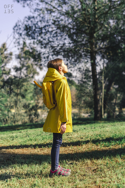 Girl wearing yellow raincoat and yellow backpack standing on a meadow enjoying sunlight