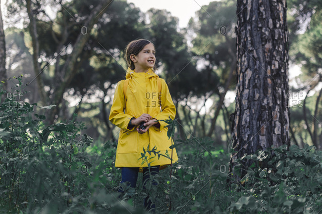 Portrait of girl wearing yellow raincoat  in nature