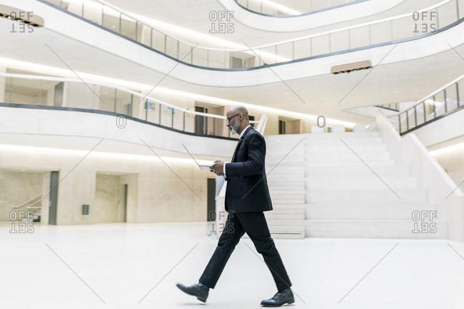 Smart mature businessman using laptop while walking through foyer