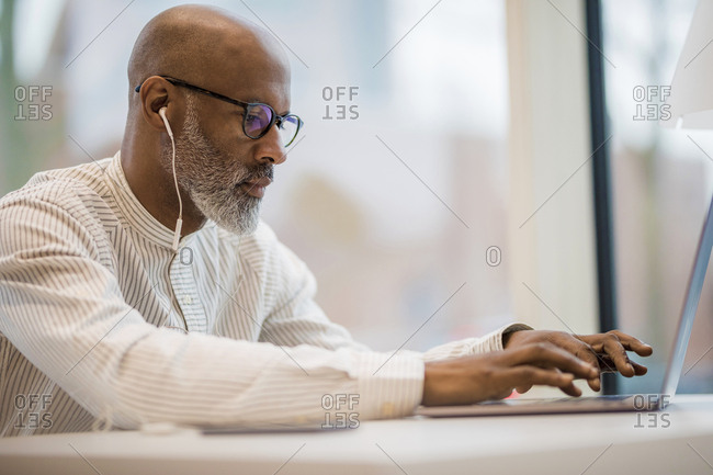 Mature businessman with earphones working on laptop
