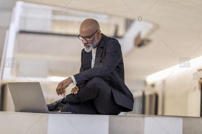 Bald mature businessman looking at laptop thinking