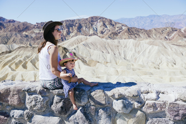 USA- California- Death Valley National Park- Twenty Mule Team Canyon- mother and baby girl sitting on wall