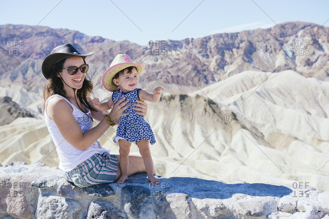 USA- California- Death Valley National Park- Twenty Mule Team Canyon- mother and baby girl on a wall
