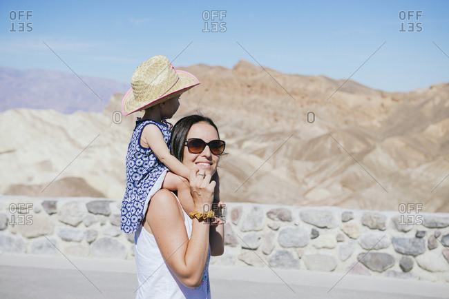 USA- California- Death Valley National Park- Twenty Mule Team Canyon-  smiling mother carrying baby girl