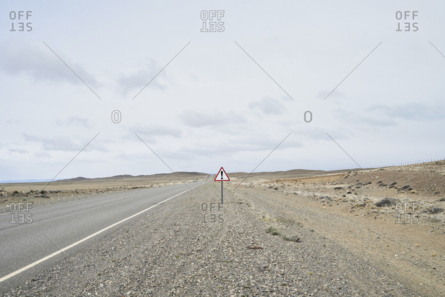 Argentina- Patagonia- Empty road with exclamation mark sign in the middle of desert