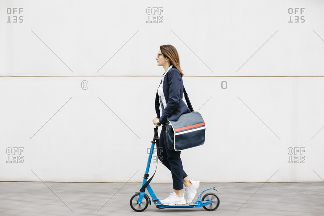 Active businesswoman riding scooter in the city