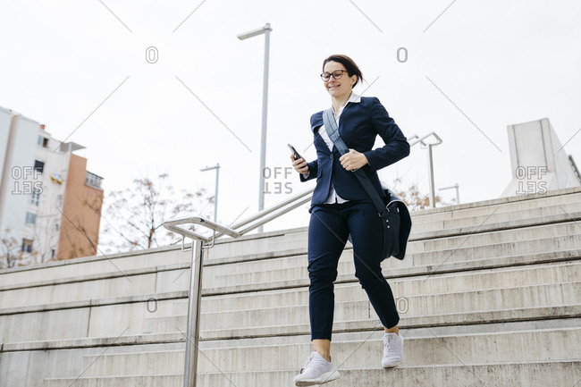 Active businesswoman moving downstairs in the city