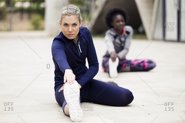 Two sporty young women stretching in city