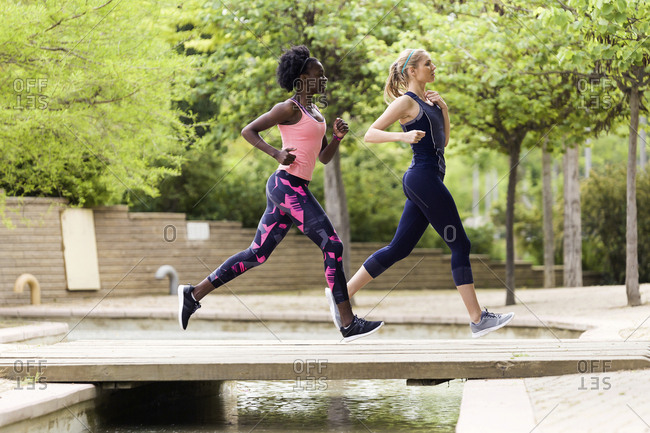 Two sporty young women running together in a park