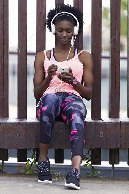 Sporty young women relaxing with headphones and cell phone