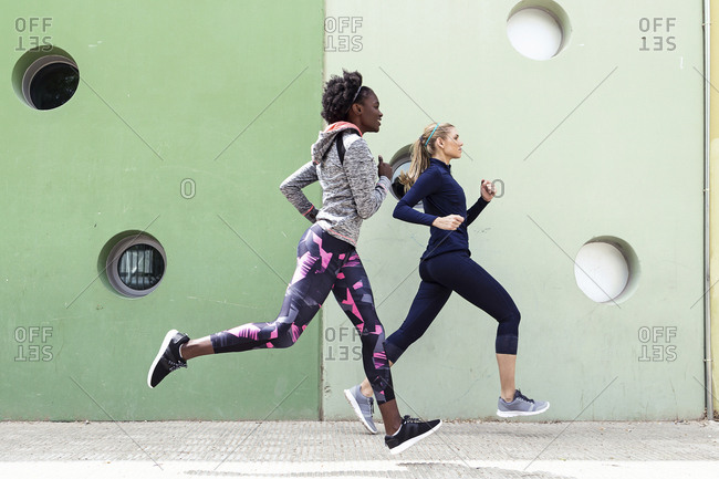 Two sporty young women running together in the city passing wall with round windows