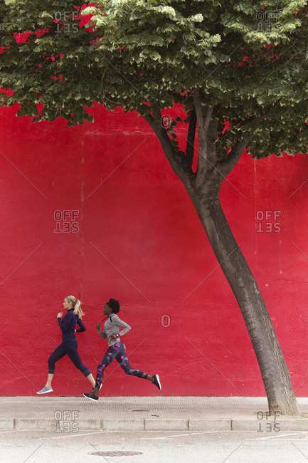 Two sporty young women running together in the city passing red wall