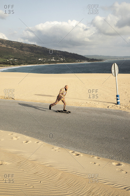 Spain- Tarifa- man wearing colorful suit skateboarding on road