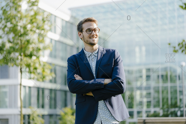 Young businessman standing in front of modern office building- with arms crossed