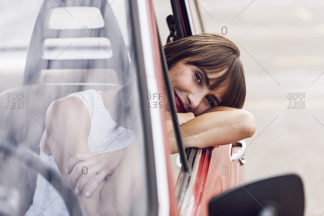 Carefree woman sitting in vintage car- smiling