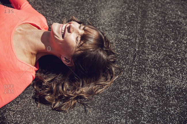 Carefree woman sitting on rooftop- lying on rooftop