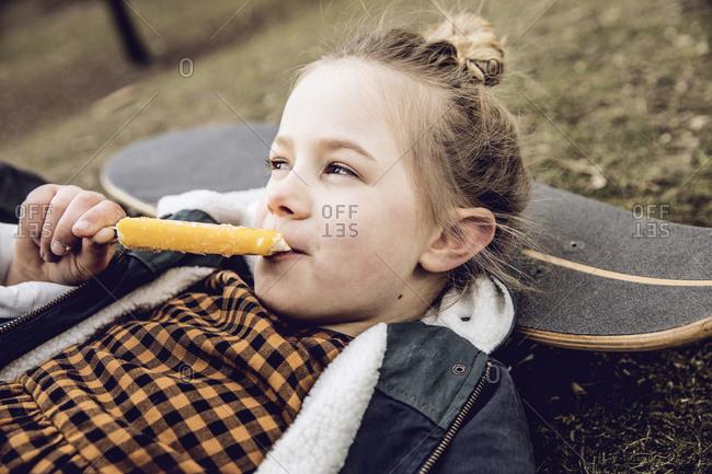 Little girl eating ice cream- resting head on skateboard
