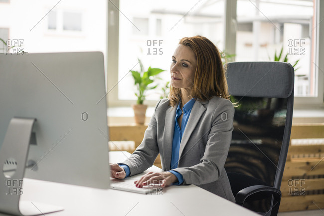 Businesswoman sitting in office- working on PC
