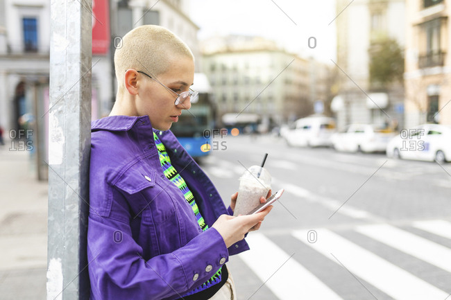Young woman leaning to a pole and texting with her phone