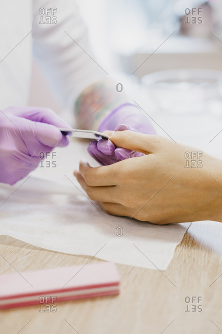 Close up of cosmetician doing manicure to a client