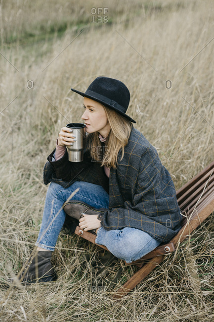 Young beautiful woman in a hat drinking coffee from a thermal mug on a walk