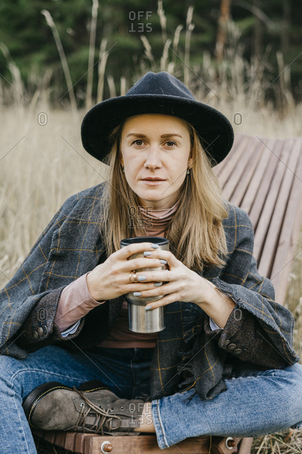 Young beautiful woman in a hat drinking coffee from a mug on a walk. looking at the camera