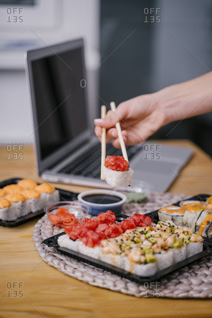 Woman eating sushi rolls at the while studying