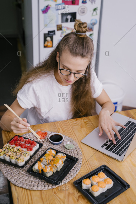 Woman eating sushi rolls at the her desk