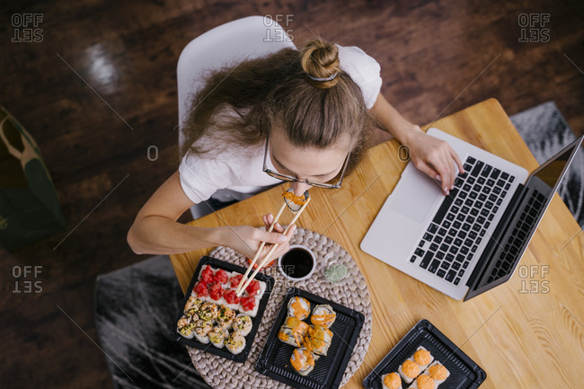 Woman eating sushi rolls in a coworking space
