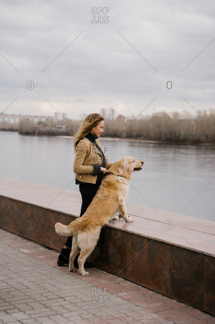 Beautiful blonde woman keeps her dog Golden Retriever on a walk in the city