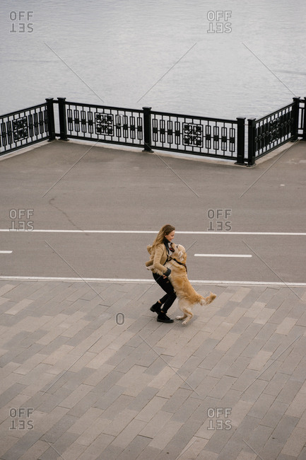 Beautiful blonde woman walking in the Park with a dog Golden Retriever walk in the city