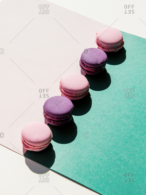 Sweet macarons in a row on pink and green papers. Side view