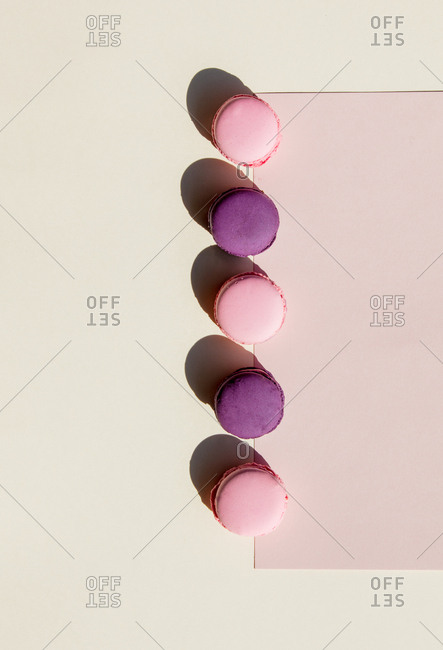 Colorful macarons in a row on pink and white background. Side view