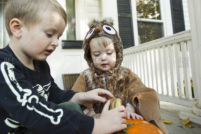 Two male children are curious about jack o lantern during Halloween